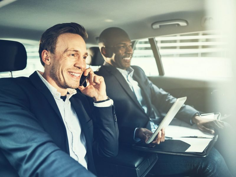 Two smiling colleagues working together while driving in the city